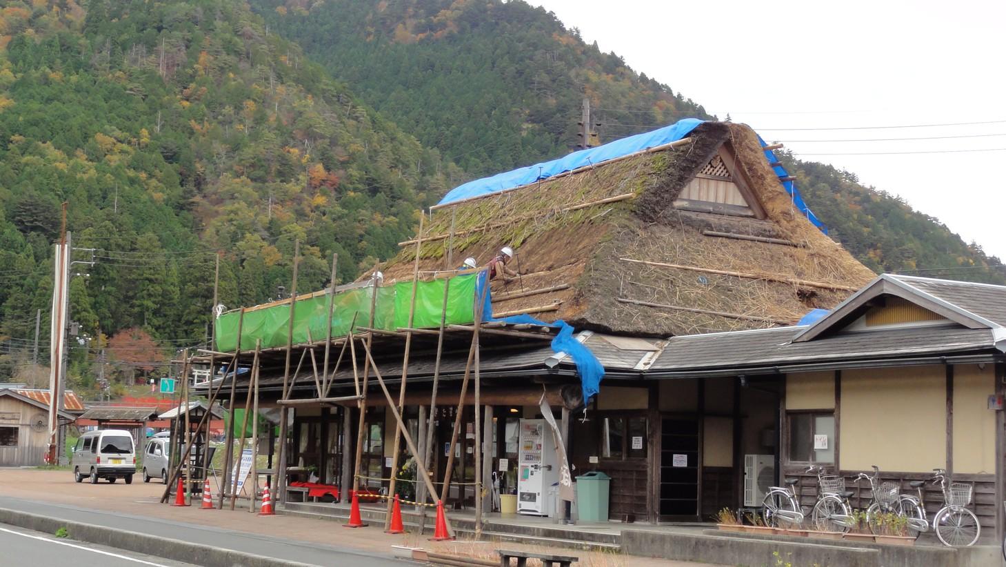 正在進行屋頂維護工程的茅草屋之里特產店